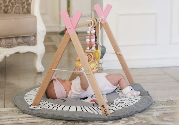 Малыш играет с детским тренажером граспи на коврике с такане и подвесами