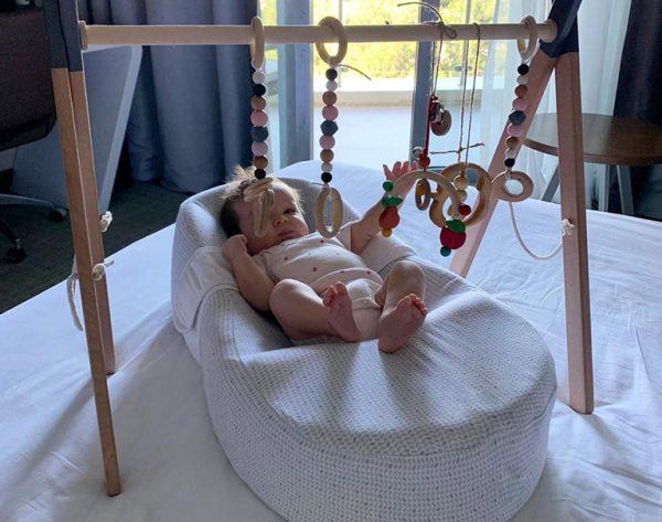 Малыш играет с граспи в коконе для новорожденных